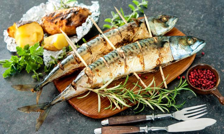 Grilled mackerel fish with baked potatoes on stone background